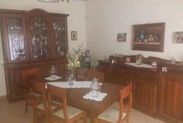 Sala da pranzo con vetrina, credenza, tavolo e sei sedie